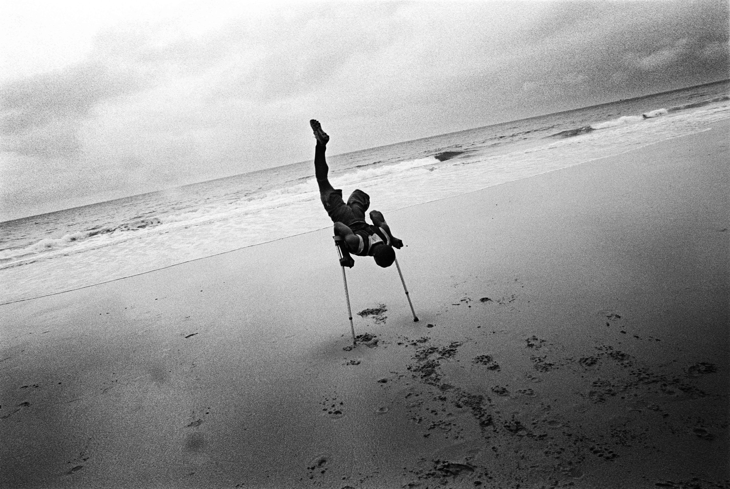 Sierra Leone, Freetown, Kalone, June 2002, A football player from Murray's Dream Team, stretching while training on the beach. Murray's Dream Team is a football team entirely made up of players with one leg. The amputee team are residents of the Murray Town amputees' camp, which is home to victims of rebel atrocities committed during the civil war.