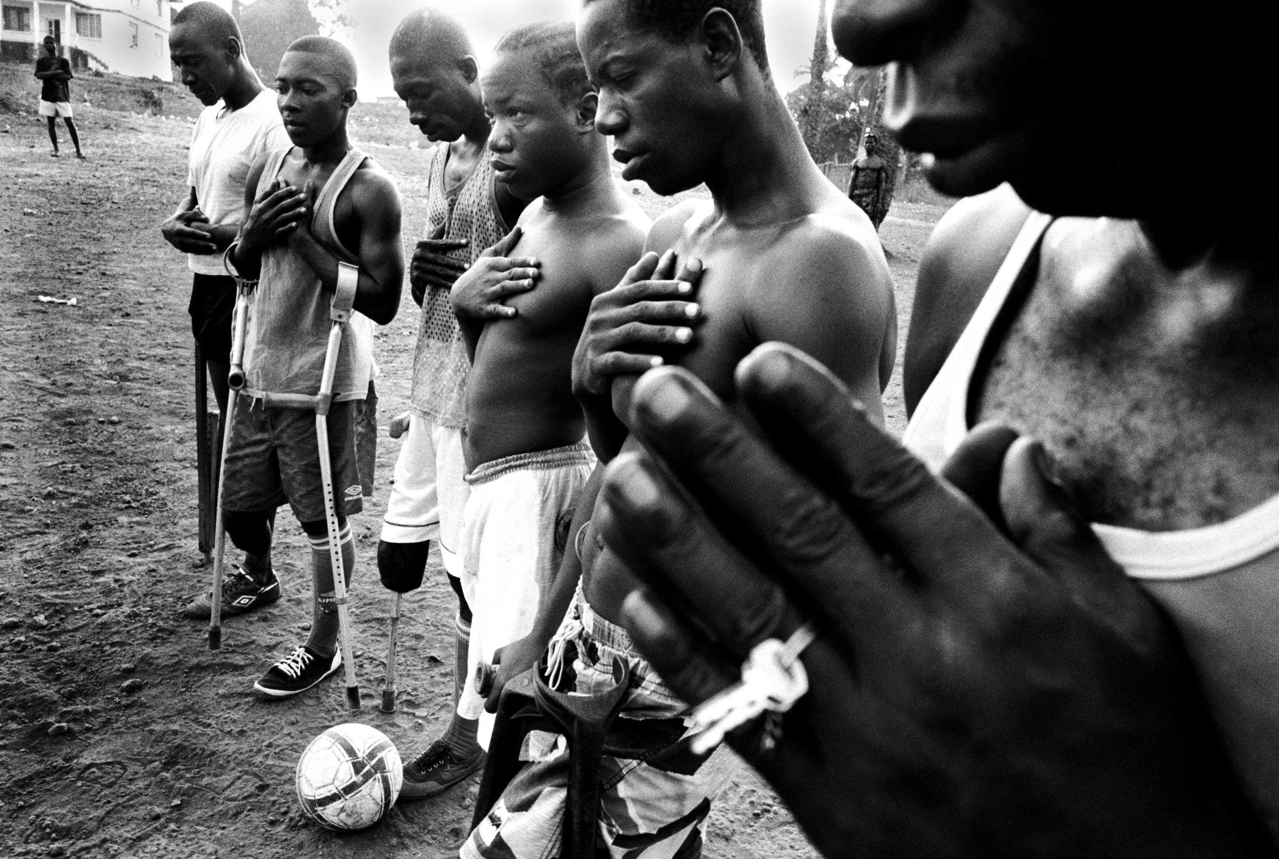 Sierra Leone, Freetown, November 2003, The team praying before the match.