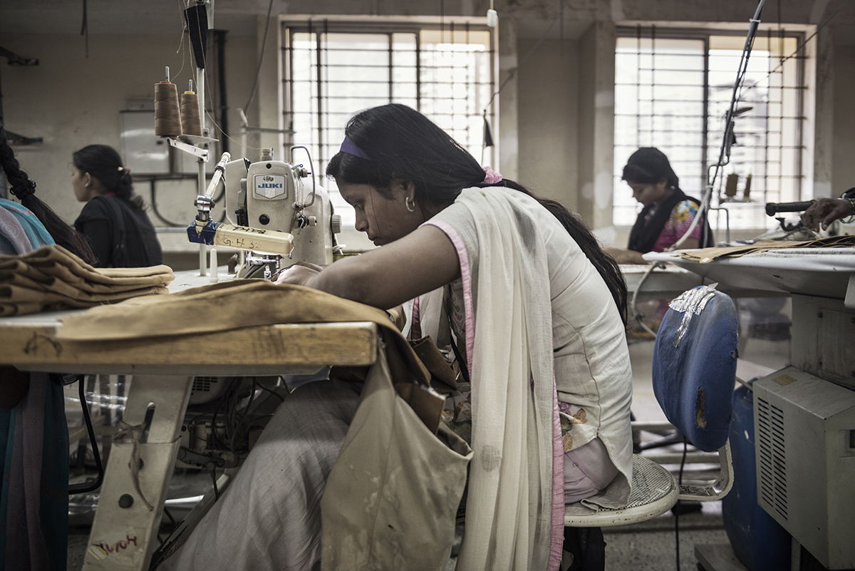 India, Bangalore, June 2016, Baidahi Tandi works on sewing details to a brown miniskirt.