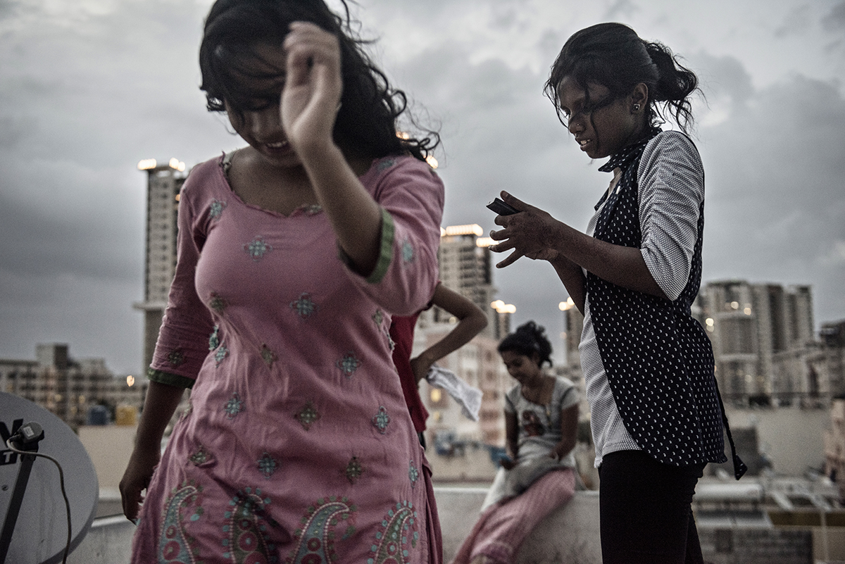 India, Bangalore, June 2016, Sima and Monali Kandi dance on the roof of the dorm where they live with other factory girls for the K. Mohan clothing factory in Bangalore, India.