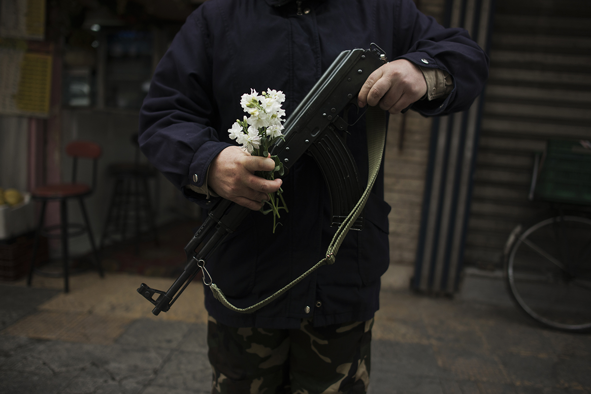 Syria, Damascus, March 2013, A Christian member of a Shabiha, men armed by Assad's government to protect their neighborhoods, holds an Easter flower while manning a checkpoint.