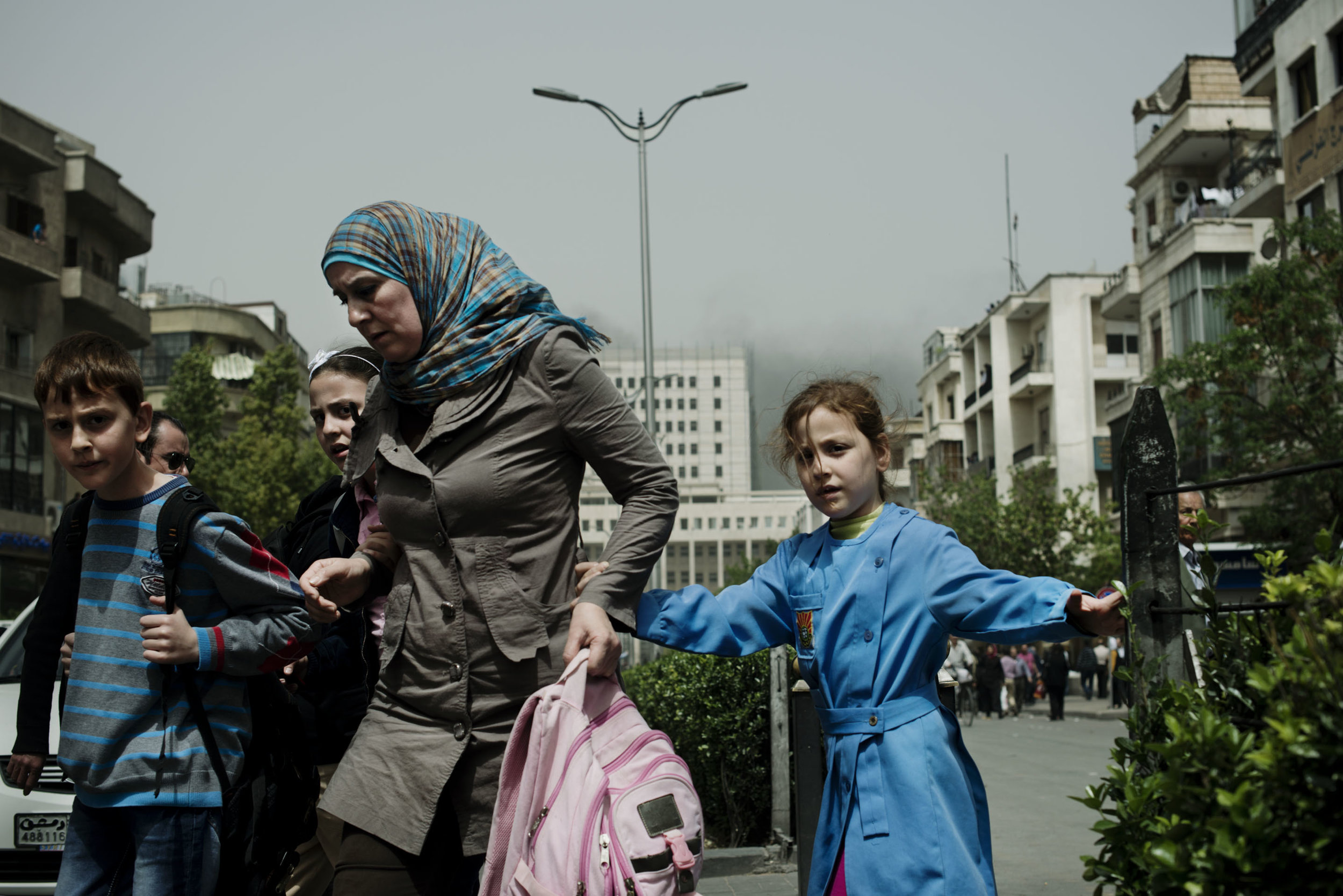 Syria, Damascus, April 2013, A woman rushes her children out of school and away from the scene of a car bomb in central Damascus which killed at least 25 people.