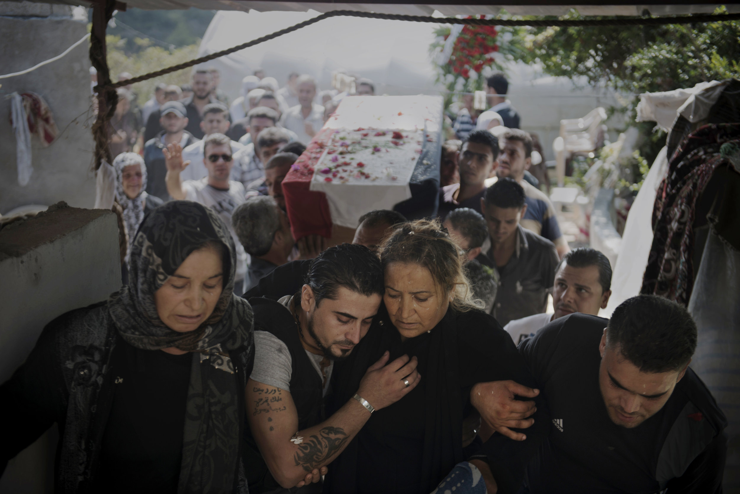 Syria, Latakia, September 2013, Bassel Barhoum (center) hugs his mother Jamila Marshid during his brother's funeral in the village of Daqaqa in Latakia Province, Syria. Abu Layth died while fighting for the Syrian Army.