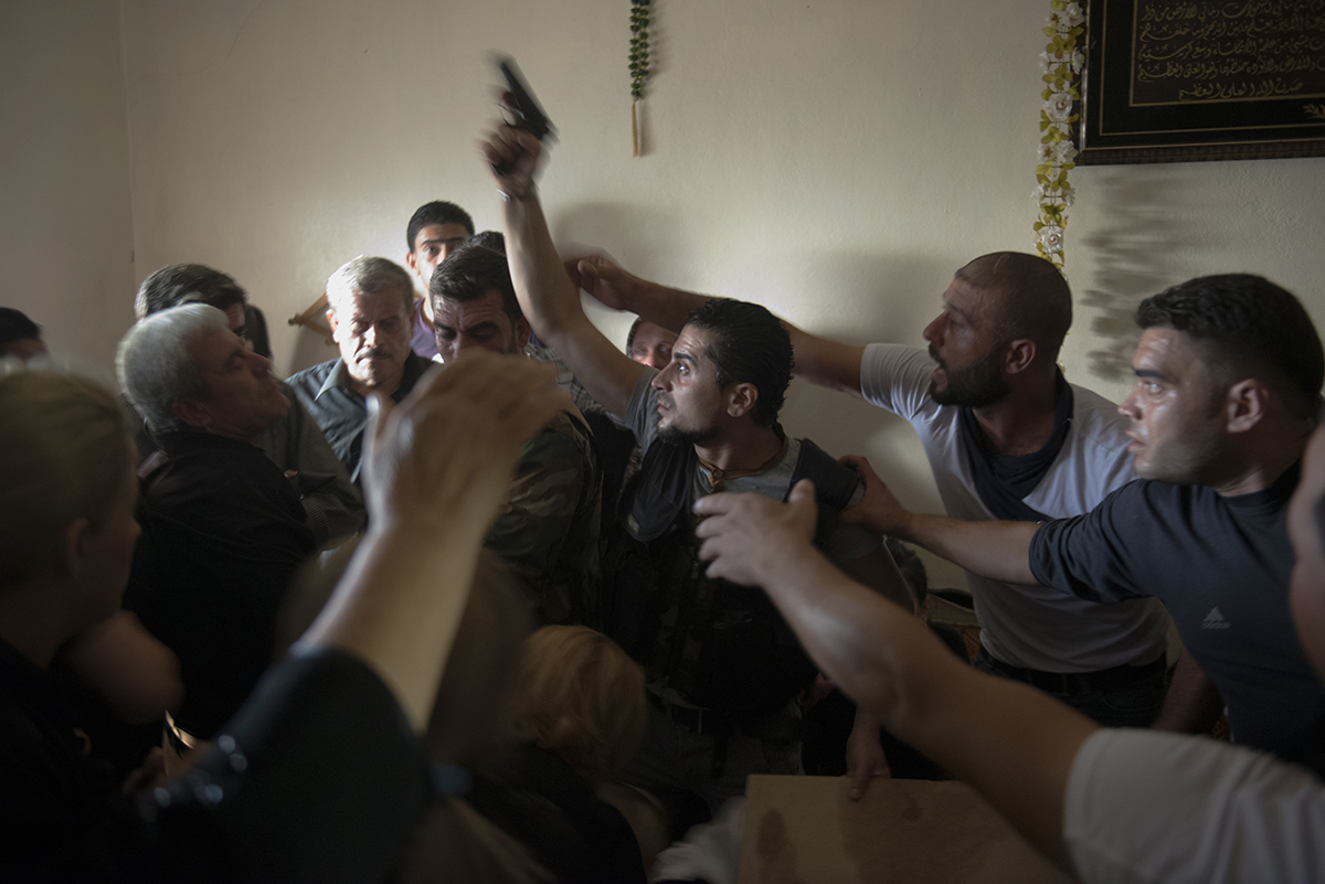 Syria, Latakia, September 2013, Bassel Barhoum (center) yells angrily after looking inside his brother's casket at his funeral in the village of Daqaqa in Latakia Province, Syria. Abu Layth died while fighting as an officer in the Syrian Army.