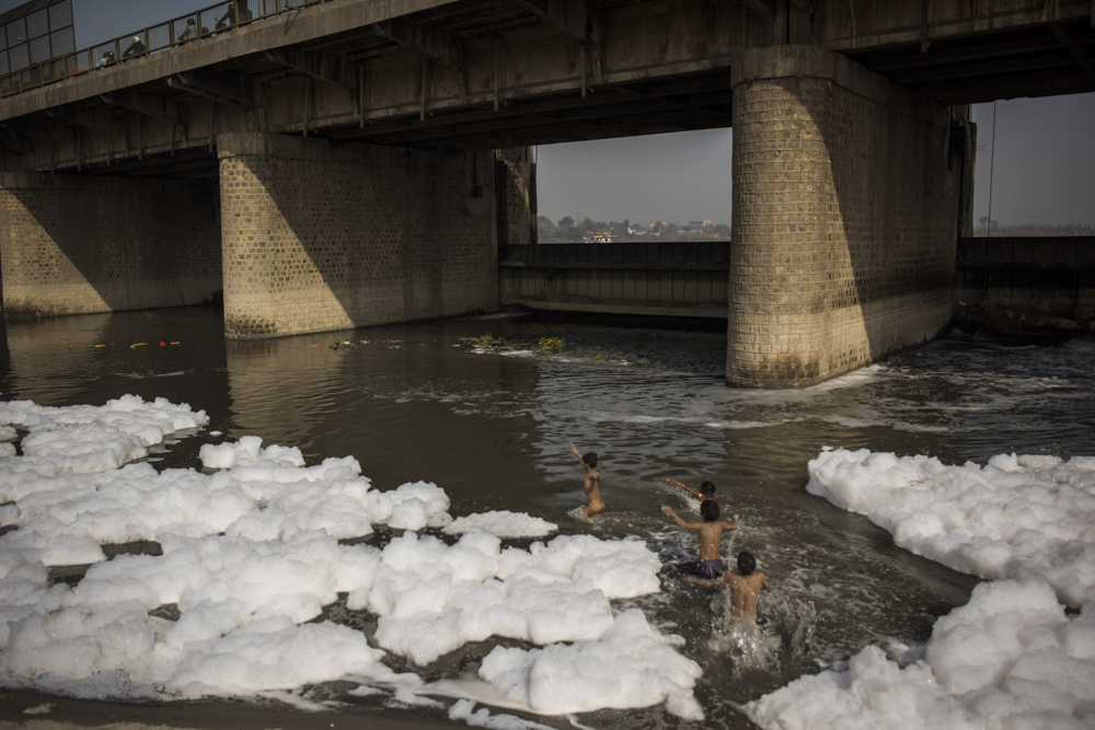 India, Delhi, Wazirabad, 08 February 2017Prakash, 10, and Raees, 11, play in the heavily polluted Yamuna River where 18 drains from New Delhi dump 600 million gallons of sewage every year. The boys thought the bubbles were signs of soap, though many people acknowledge that the bubbles are from sewage and industrial runoff.Andrea Bruce / NOOR