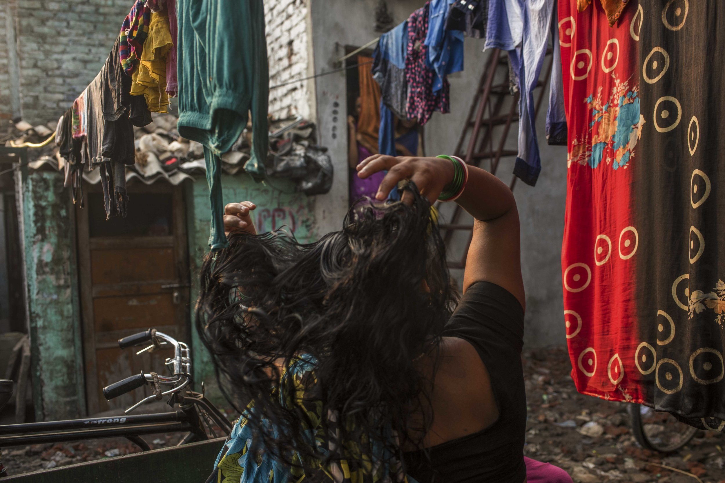 India, New Delhi, October 2016, A young woman dries her hair.