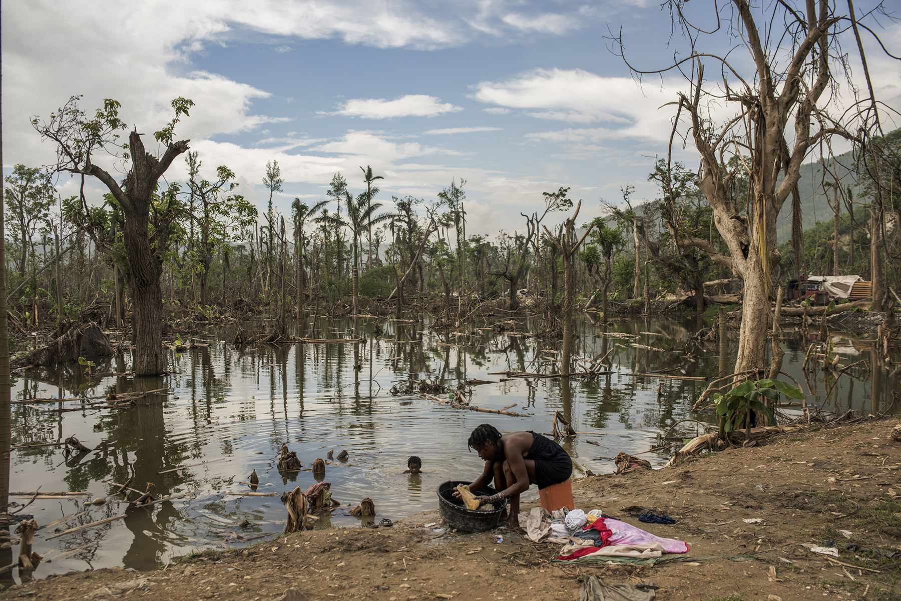 Haiti, Les Cayes, 16 November 2016, Surrounded by the destruction caused by Hurricane Matthew, Pharana Pierre washes clothes while her daughter Carla Michele, 6, plays in in the water.