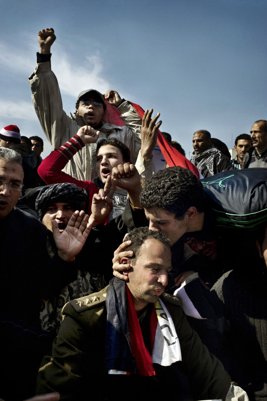 CAIRO,  EGYPT--  FEBRUARY  02,  2011:  A  demonstrator  kisses  Captain Ehab Fathi  (in the  military  uniform) who  joined the  protest  calling  for the  removal of President Hosni Mubarak in Tahrir Square.