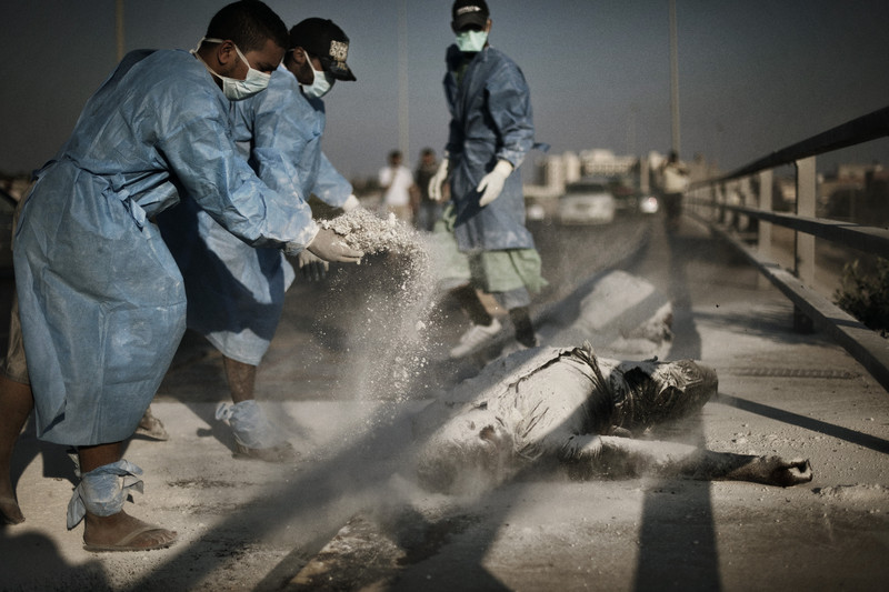 Rebel volunteers sprinkle chemical powder on a pair of corpses in the al-Intisar neighborhood of Tripoli. Volunteers have moved throughout the Libyan capital in recent days, removing corpses and garbage that were inaccessible during several days of fighting between rebel forces and those of Col. Gaddafi's.