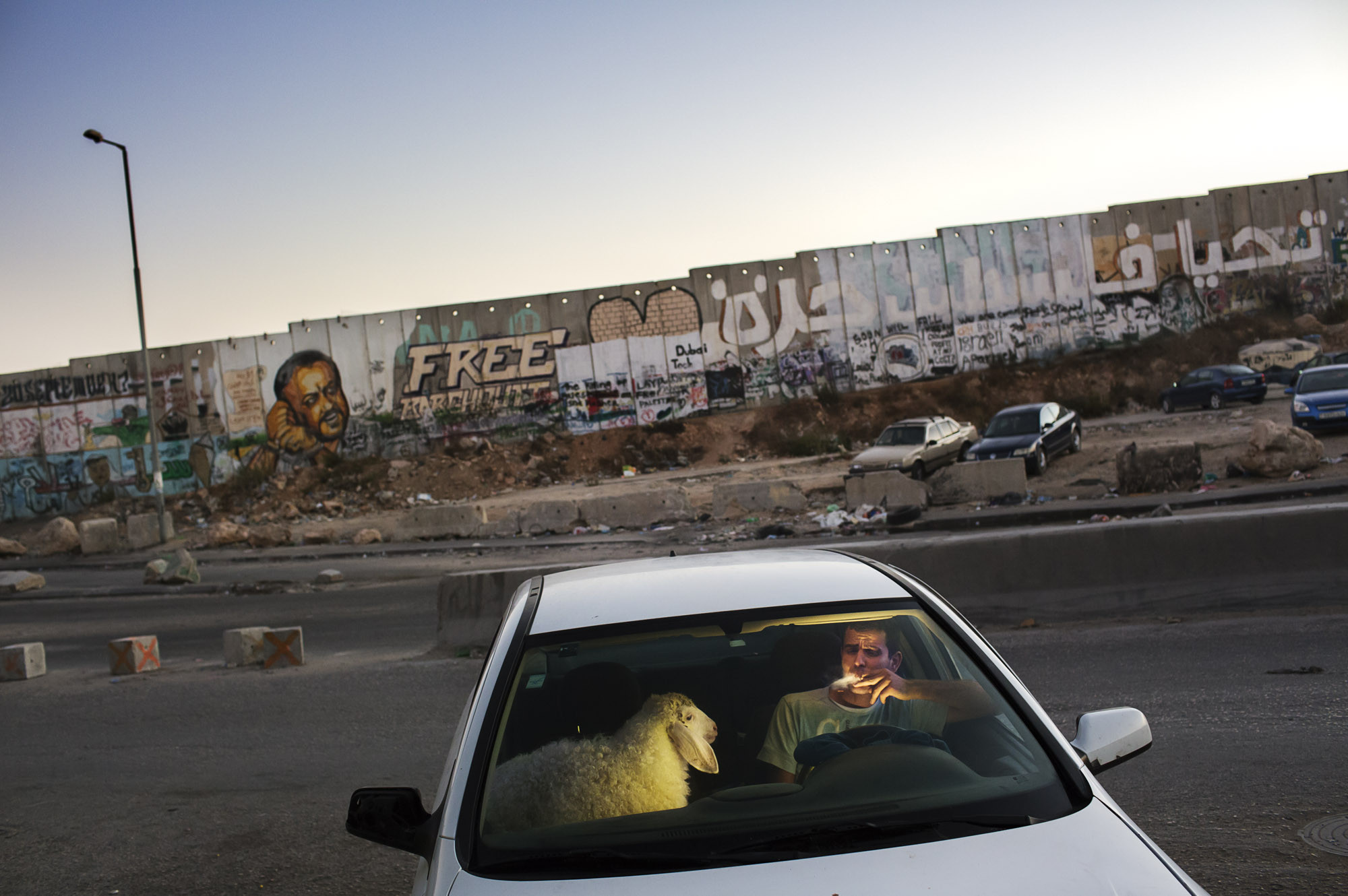 Occupied Palestinian Territories, West Bank, August 2013, After grueling traffic at the Qalandia checkpoint, a young man enjoys a cigarette in his car as traffic finally clears on the last evening of Ramadan.