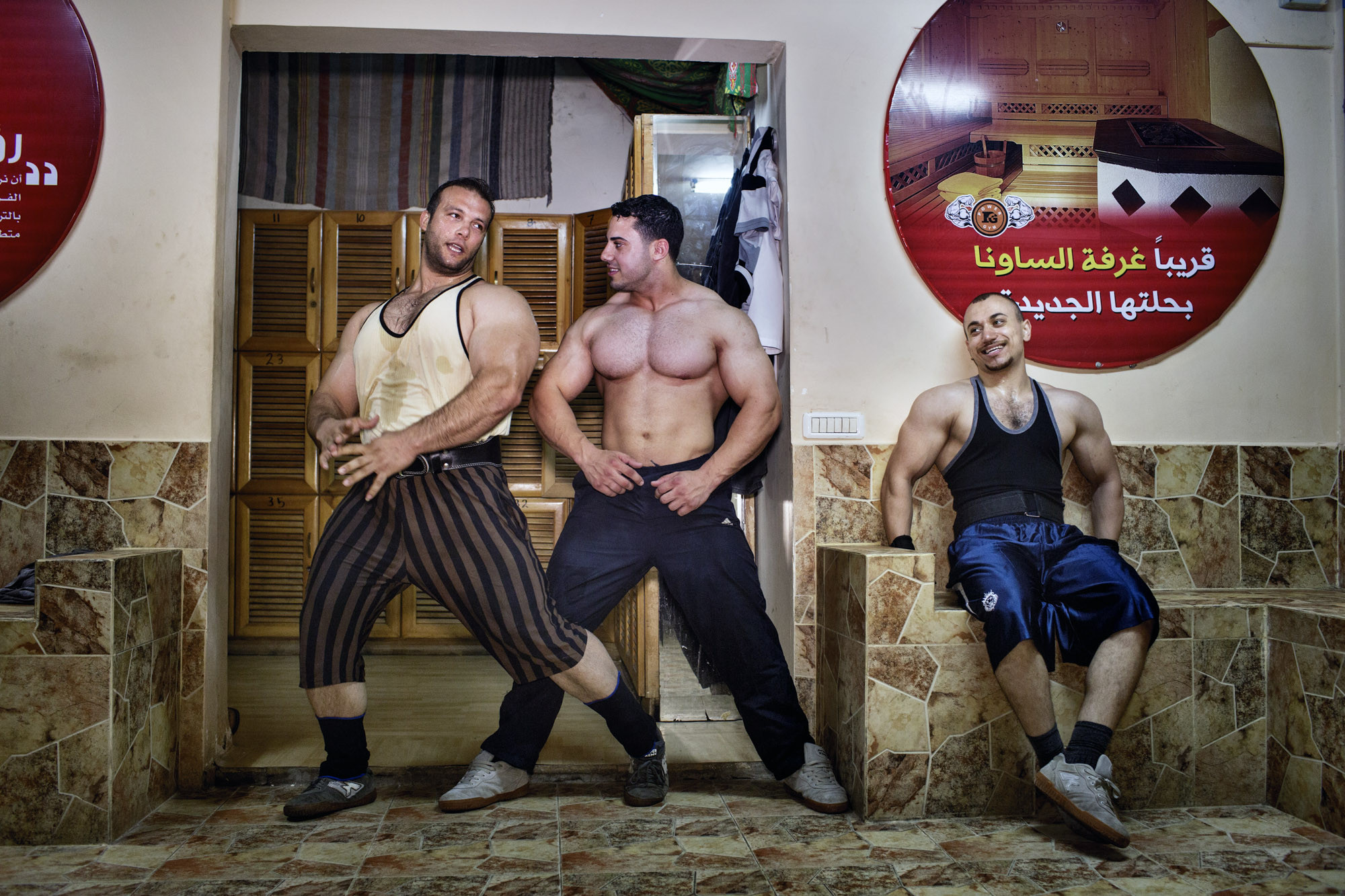 Occupied Palestinian Territories, West Bank, June 2013  Gazan body builders jovially strike poses after a workout.