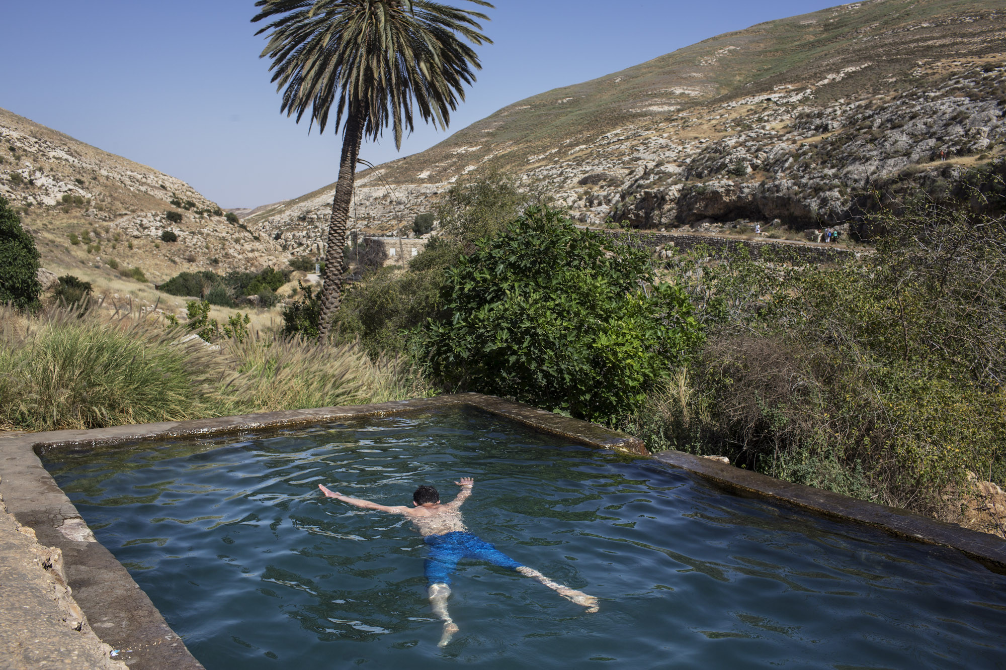 Occupied Palestinian Territories, West Bank, Ein Farah, April 2013, A Palestinian youth from Hebron enjoys a swim in Ein Farha, considered to be one of the most beautiful nature spots in the entire West Bank. It, like many other nature reserves and heritage sites, is occupied by the Israeli Nature and Parks Authority. Palestinian tourist enterprises are not allowed.