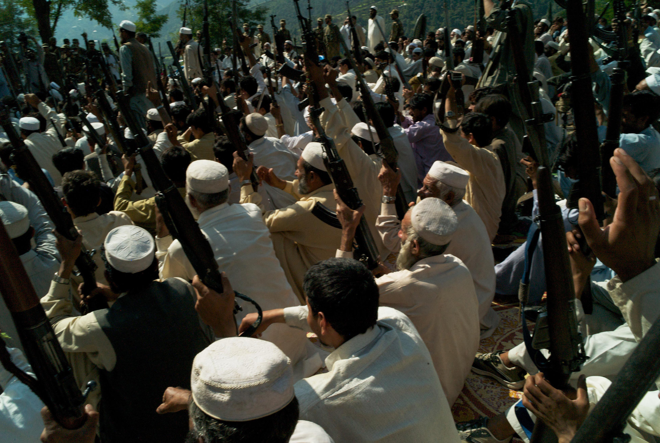 PIOCHAR, PAKISTAN- SEPTEMBER 2009  Raising their rifles in a show of strength, men from the village defence committees of the Piochar Valley gather together as a lashkar (traditional army) is raised to rid this remote corner of Swat from the Taliban. Men in all twelve union councils of Swat have been encouraged to take up arms and fight in conjunction with Pakistani security forces as fighters from Maulana Faizullah's Tehrik-i-Taliban continue to terrorise this mountainous region.