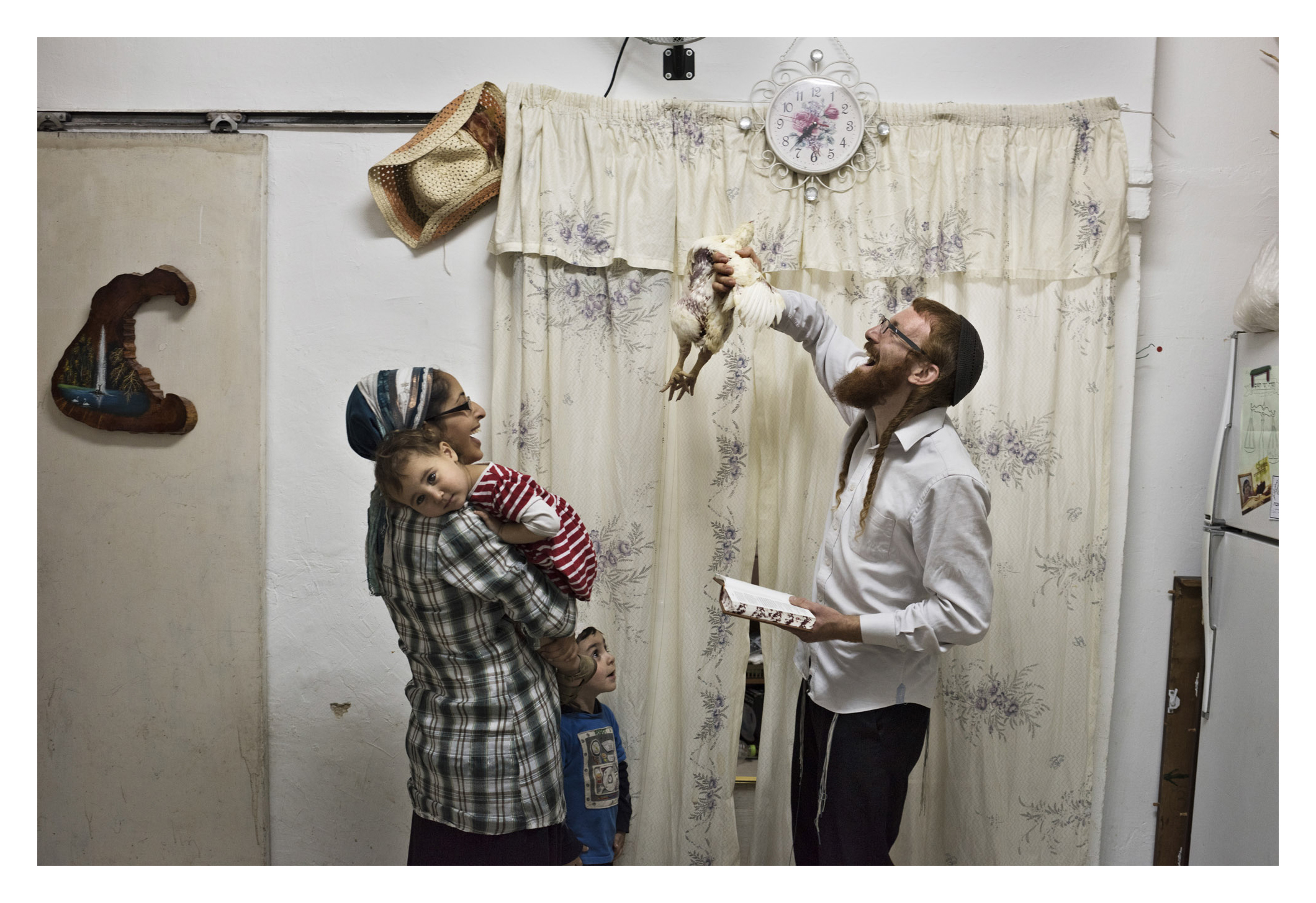 """Yossef is a follower of Rabbi Nachman of Breslav, a lighter, more mystical version of Judaism that appears stringent to secular Israelis but is borderline psychedellic to the ultra-Orthodox neighborhood of Mea Shearim, where he was born and raised. He buys a chicken for the yearly """"kaparot"""" ritual - the passing of one's sins onto a chicken that is ritually killed and is given to the poor for a holiday meal. Yossef loves animals; he always brings home strays, despite orthodox Judaism's ambivalent approach to pets, and normally he donates money to charity directly, but this year he wanted to acquiant his son with the sacrifice. He talks to the chicken, feeds it a children's snack and solemnly wipes its bottom when it defecates on his spotless kitchen floor. He works in real estate and is about to move to a settlement; he's not into politics but says atmosphere there is so much more liberal than in the largely anti-Zionist, ultra-conservative Mea Shearim. The chicken flutters onto his shoulder. He grabs it by the feet, gently spinning the chicken over his sons head while reading the relevant invocation; and walks it off to slaughter."""