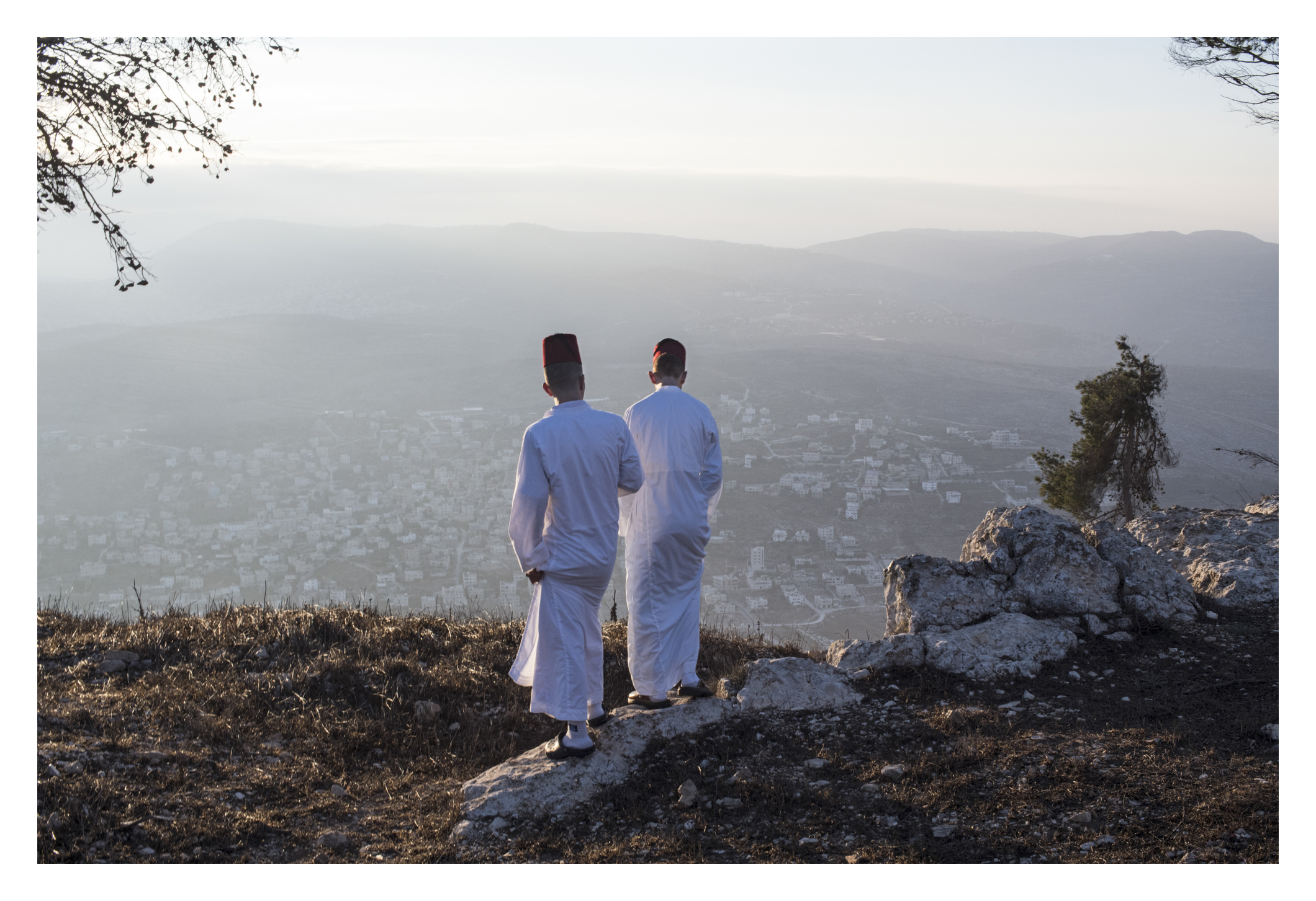After the final prayer with book , youth of assorted ages and men take a pause on mountain and relax, overlooking the view of mountain after sunrise. Here, they are standing near the enclosed area they say is where Isaac's father was tested for sacrifice. (daniel, please read)Share a deep dive into the world of the Samaritans, an ancient sect in the West Bank. The story follows an Samaritan historian/spokesperson as he tries to find some valuable antiquities that were stolen from their temple. The story is about ancient bible manuscripts stolen from the Samaritans' synagogue in the West Bank, and the quest to track them down and discover who stole them. The story goes deep into the world of the Samaritans, one of the world's oldest and smallest religious sects, and how their ancient Torah manuscripts are central to their identity. The sunrise pilgrimage on Wednesday is a dramatic visual example of what makes this sect unique and mysterious, and why they prize their Torah manuscripts, with a  Samaritan priest thrusting a silver-cased Torah scroll into the air as Samaritans surround him atop their sacred mountain. Currently, the population of Samaritans living in the community in Mt Gerizim is  800, and they only do an exact count each January 1. The numbers will be updated by end of this year. It all begins in the Mt Gerizim synagogue, wailing and praying from 2 am before they leave and begin marching to peak of sacred mountain.This happens just before sunrise, at 4/4:30, for hours of prayers and rituals around the sacred book, along with a stunning sunrise pilgrimage on the Samaritans' holy mountain. A Samaritan priest thrusts a silver-plated torah scroll toward the heavens, surrounded by the samaritans. Several times this repeats  during the service.
