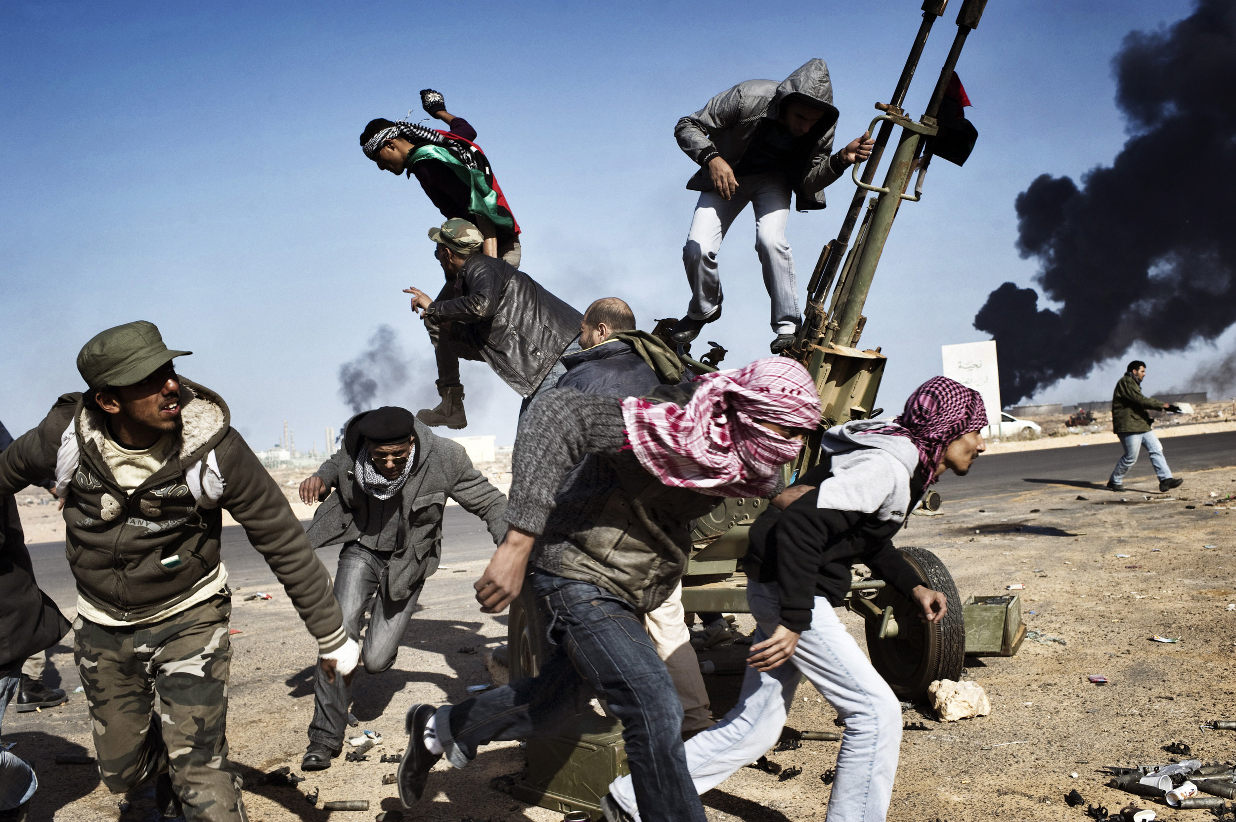 RAS LANUF, LIBYA - MARCH 11: Rebels flee under fire from the Libyan army