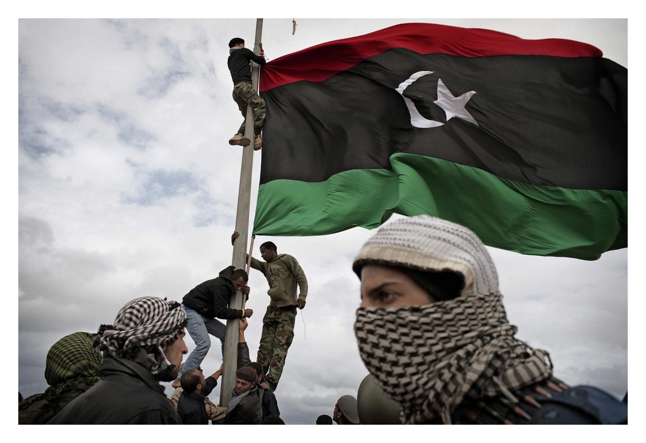 RAS LANUF, LIBYA - MARCH 08 2011: Libyan rebels raise their flag at a checkpoint in Ras Lanuf RAS LANUF, LIBYA - MARCH 08: Libyan rebels raise their flag at a checkpoint in Ras Lanuf