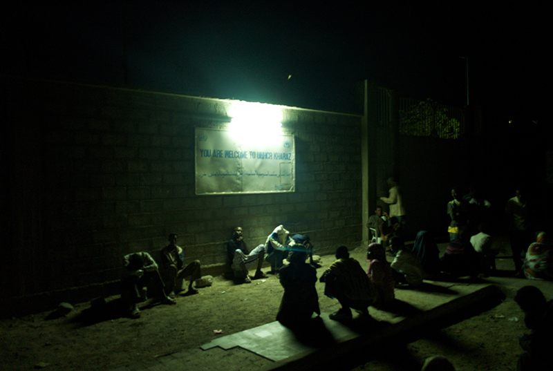 """Al-Kharaz, Yemen - April, 2008. Utterly exhausted, a group of Somali refugees crouch down beneath an illuminated signboard reading, """"You are welcome to UNHCR Kharaz""""."""