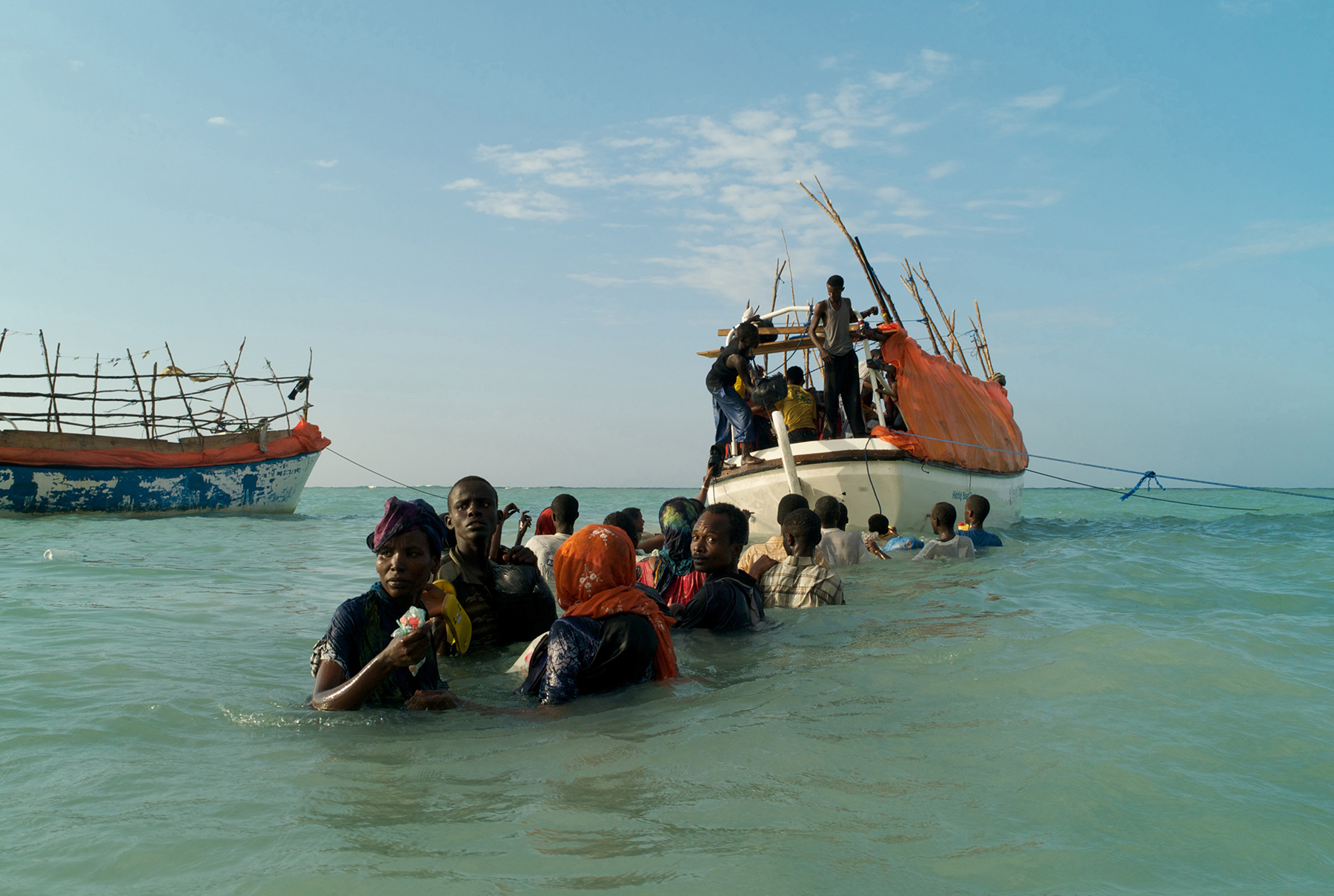 Shimbiro, Somalia, November, 2007. Standing in choppy shoulder deep water, Somali refugees look back anxiously from the sea as they try to locate friends and relatives left behind on Shimbiro Beach. Preparing to board one of three smuggler's boats that will depart simultaneously for Yemen, many of the passengers have become separated from those that they had hoped to make this high-risk journey with.