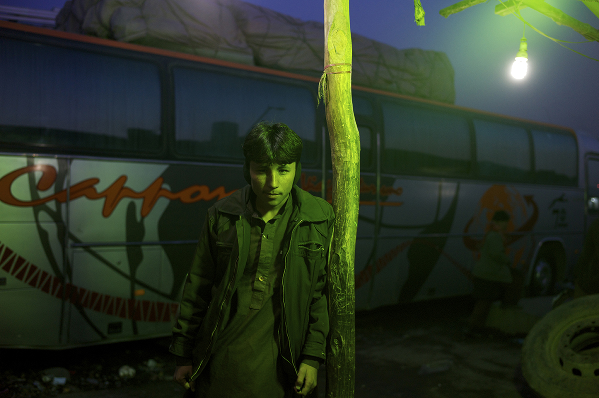 Afghanistan, Kabul, December 2011, Under the green fluorescent lights of a shelter, a teenage traveller in ear muffs waits outside a mosafer khana in the grounds of the Company area bus station.