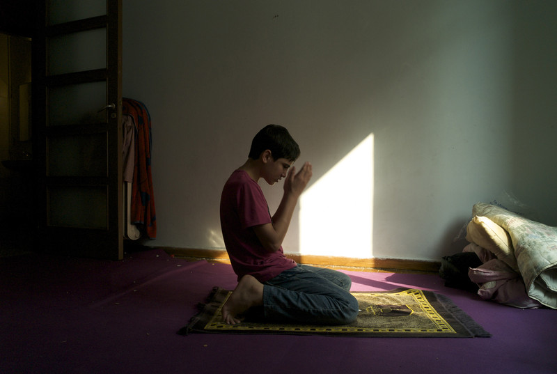 Greece, Athens, October 2011, Facing Mecca and the world outside, thirteen year old Gulistan kneels down on a mat as he says his prayers at Asr in the flat of his smuggler in Athens that is now a temporary home to fifteen Afghans.