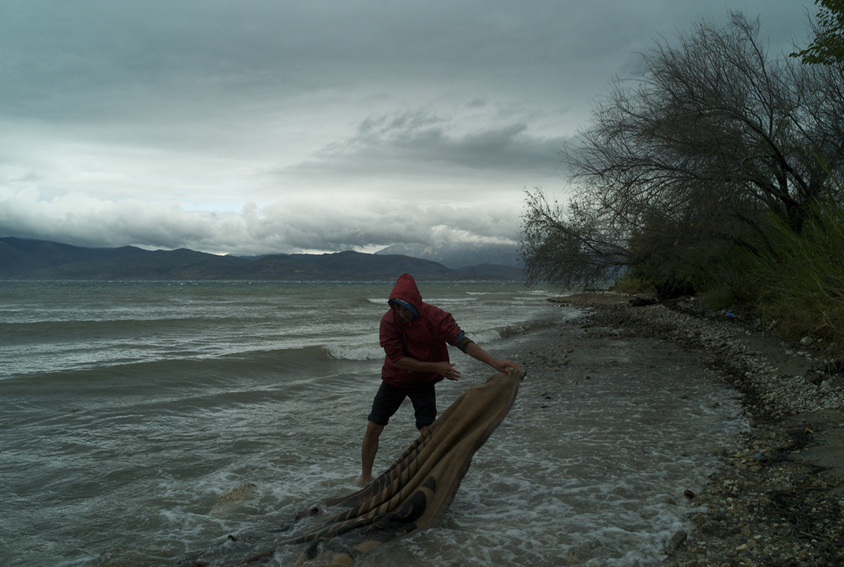 Greece, Patras, October 2011, Bracing a fierce gale, eighteen year old Mohammad Isa heads out into the sea under stormy skies to wash his blanket that was blown away into the mud during the storms that have torn through Western Greece over the past days.