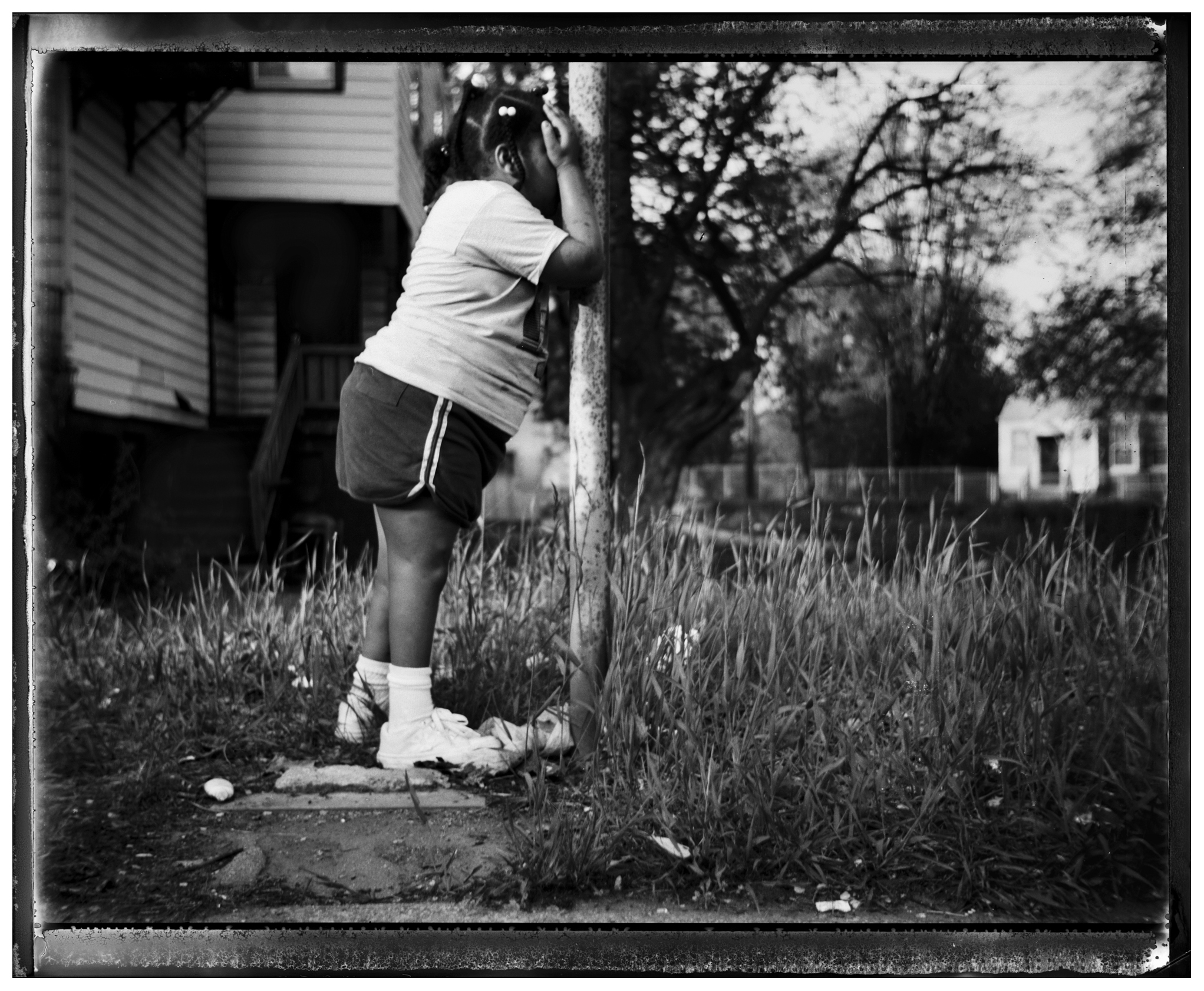"""Mariah Driver plays Hide and Seek with her sisters outside her house on S. Chicago St. in Chicago's Pocket Town neighborhood. The family has since moved to the Englewood neighborhoodand the house, which was in decrepit condition, has been demolished to make way for new development by the Comer Foundation. This is a story about place. Pockettown, or """"the Pocket,"""" is a tight-knit African-American neighborhood in the Greater Grand Crossing neighborhood on Chicago's South Side. In 2001, Gary Comer, founder of Lands' End and a Pockettown native, asked me to teach photography at Paul Revere Elementary School and to document life in the neighborhood.  A Revere alumnus, Comer was providing substantial resources through his foundation to his alma mater and childhood community, which had shifted from a white ethnic area to a predominately black neighborhood. I agreed.  In January 2002 I began working at Revere and in the community.  For the first 18 months I photographed primarily within the school.  But I felt that my role needed to be more than a photographer, so I also coached basketball and worked on a community newspaper.  As I became more known, I started to concentrate on life outside the school.  Since 2000 the South Side has seen major changes, including the destruction of many Chicago Housing Authority projects and the continued gentrification of many communities bordering Lake Michigan.  As part of documenting life in the Pocket, these photographs attempt to illustrate larger trends of renewal, change and transformation on the city's South Side. The project also includes audio interviews with neighborhood residents that record their feelings about the changes occurring in their neighborhood. My hope is to stimulate dialogue about inequitable access to education, jobs and housing-in short, about opportunity and the meaning of community. I have few answers to these questions, but I'm not done looking.   Before the mid-1950's it was a pr"""