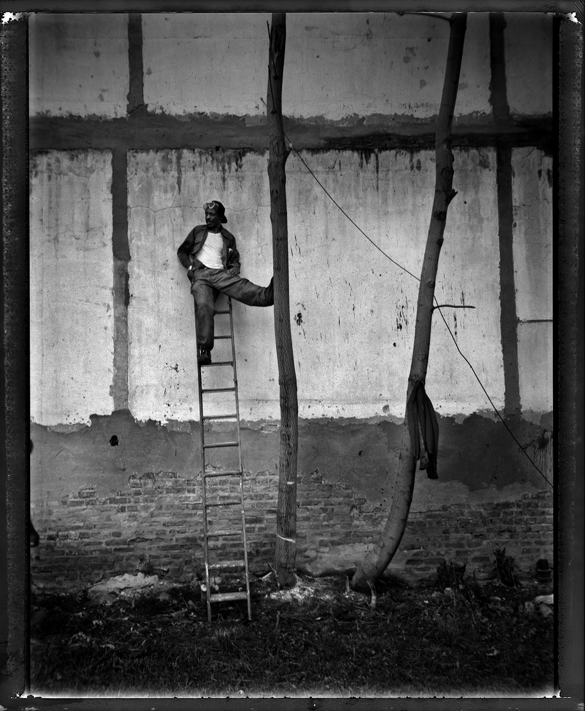 USA, Chicago, May 2006, Man stands on ladder while waiting for a chainsaw to arrive on the 7100 block of Dobson.