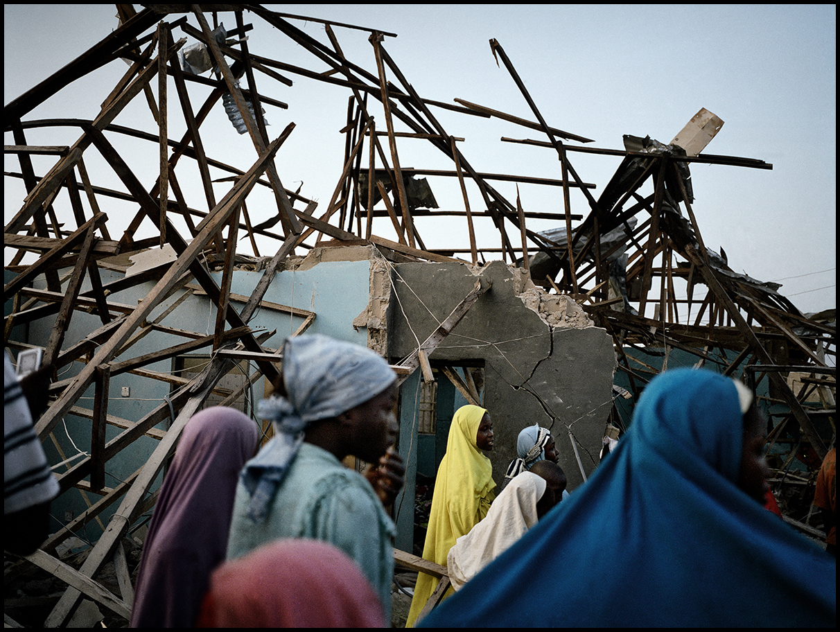 Nigeria, Mando, December 2011, Young girls look at the damage caused by the explosion of homemade bomb, kept in a private house.