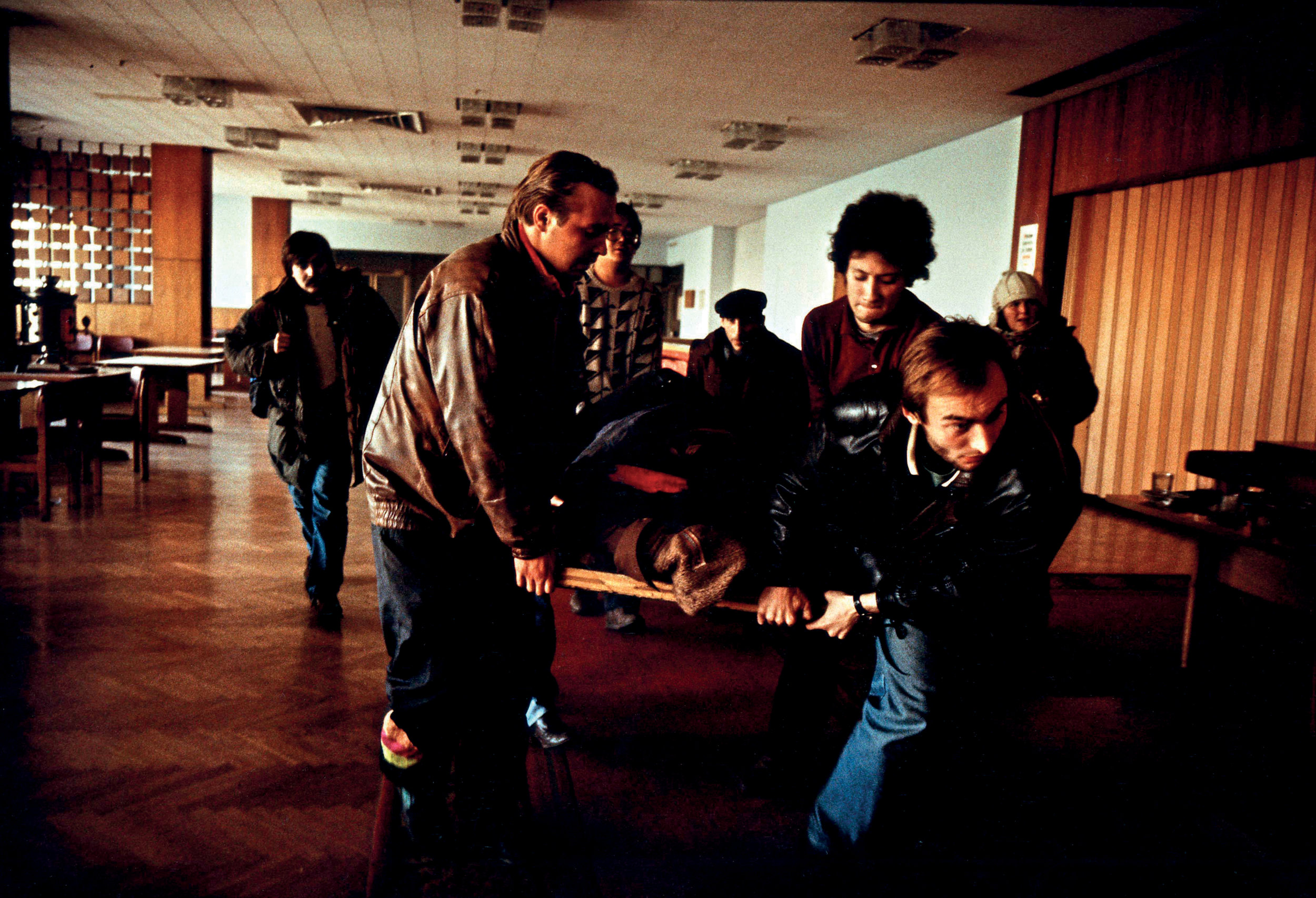 Russia, Moscow, 1993, People carrying an injured person on stretcher. Hundreds of rebels were herded out of the devastated building by troops as Yeltsin and the world breathed a sigh of relief. But scores of others left under white sheets. The official Kremlin death toll for the two days of fighting was 142; all but 21 were civilians.