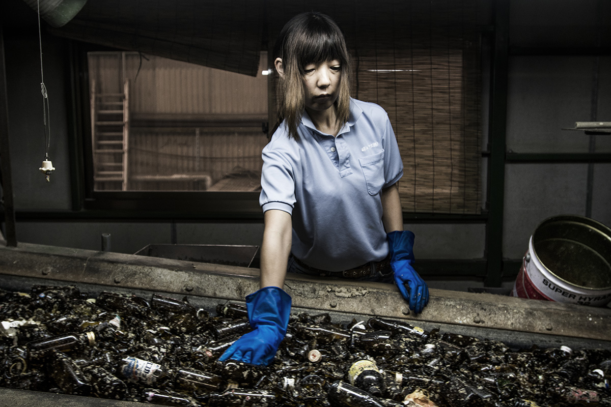 Japan, Ryugasaki, August 2016, Showaglass recycles glass bottles. 350 tons / day, 420.000 tons / year. 72% commercial and 28% household. Kaori Kimchi (48) has been working at the company since 2001. She is from Inashiki city. She removes dirt which is between the glass bottles.
