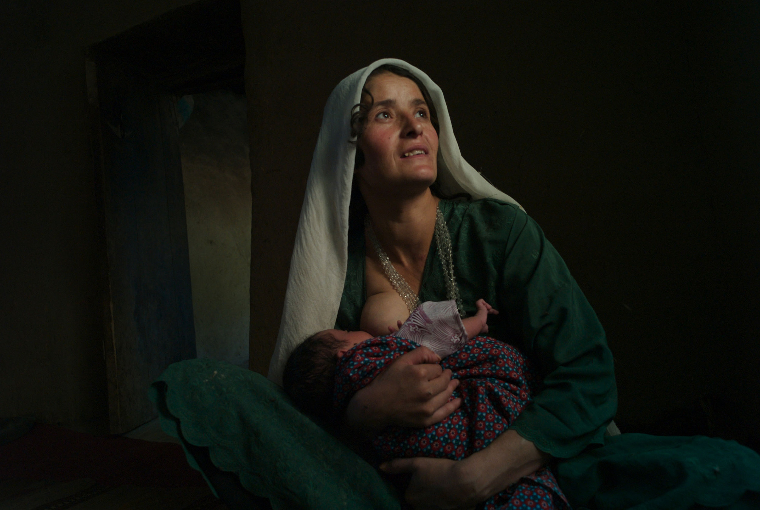 Afghanistan, Shahr-I-Buzorg, August 2008, Siamoy breast feeds her month old baby boy Hokim as she goes to visit her sisters at their home in Khourdakon village. Situated in the remote mountainous province of Badakshan, the area has the highest rate of maternal mortality in the world.