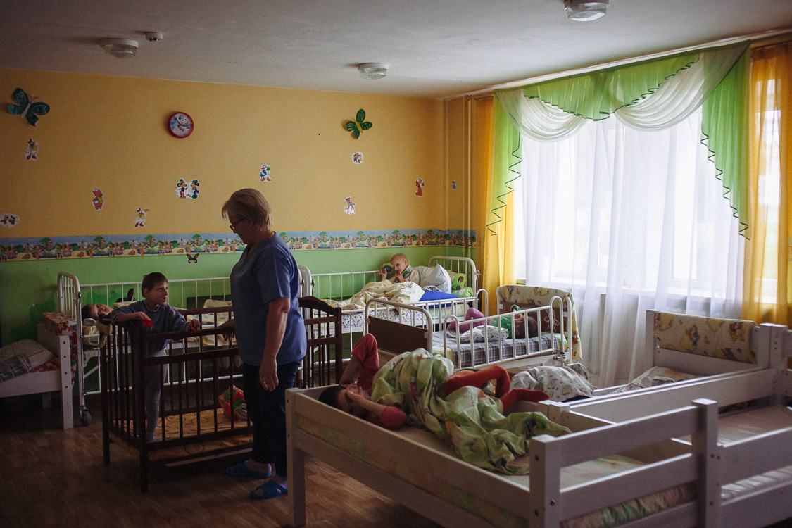 Nurse communicates with one of the children that lives  in the orphanage for disabled children with special psychophysical development. October 10, 2016, Minsk, Belarus.Most of the time in the orphanage, the children are alone with themselves. At night in a boarding school, one nurse at a 24-hour post, who does not have the right to prescribe any medicines to children, even in emergency conditions.