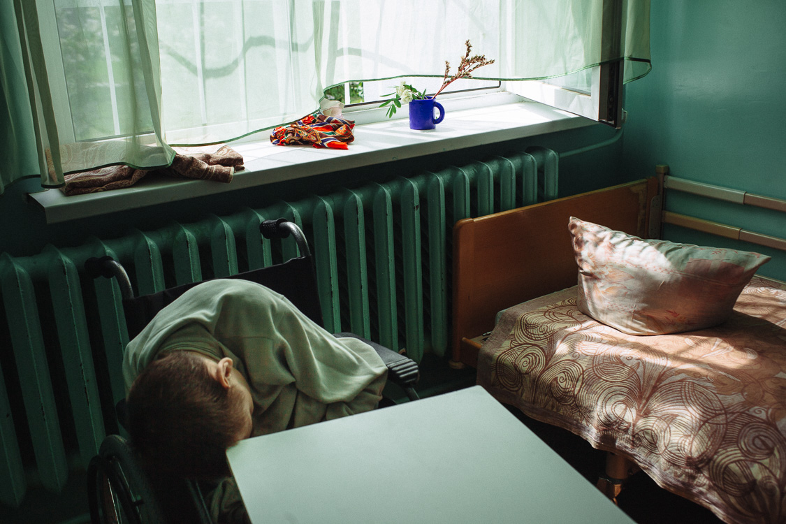 Residents of the psycho-neurological residential care facility for the elderly and disabled #3 in his room. May 24, 2016, Minsk, Belarus.Many of the residents lie all the time, which causes atrophy of all muscles. In the orphanage there is no rehabilitation therapist and massage therapist, which are necessary for such people.