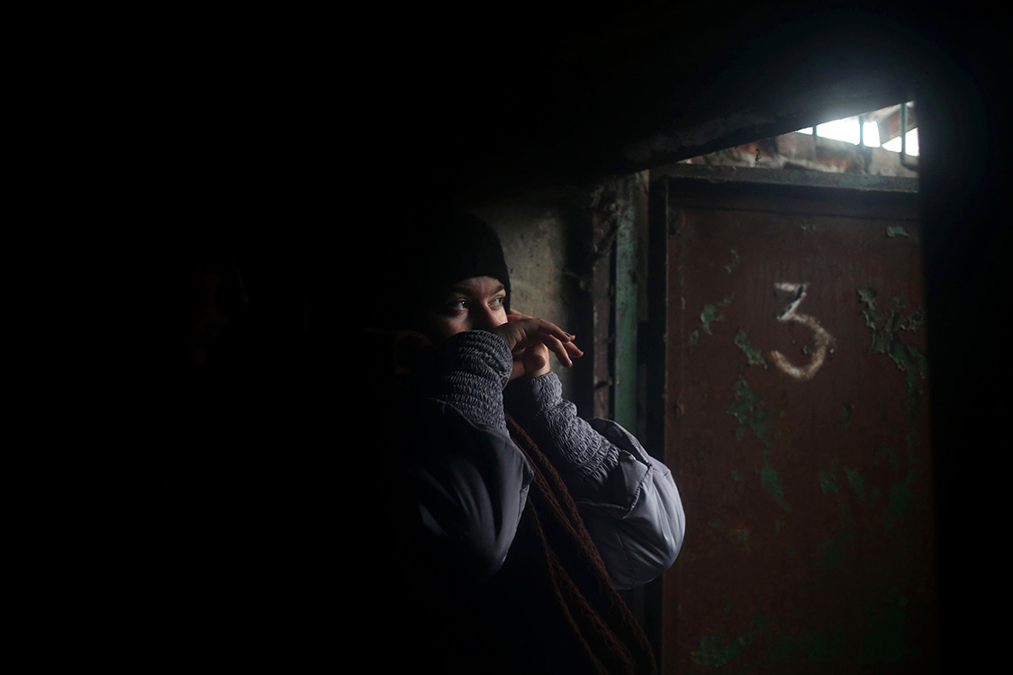 I was working in Debaltseve town during the hostilities in January-February 2015. I was walking on the street when the shelling started. People were rushing to the basement to hide. In this photograph a woman is hiding in the basement from the shelling.