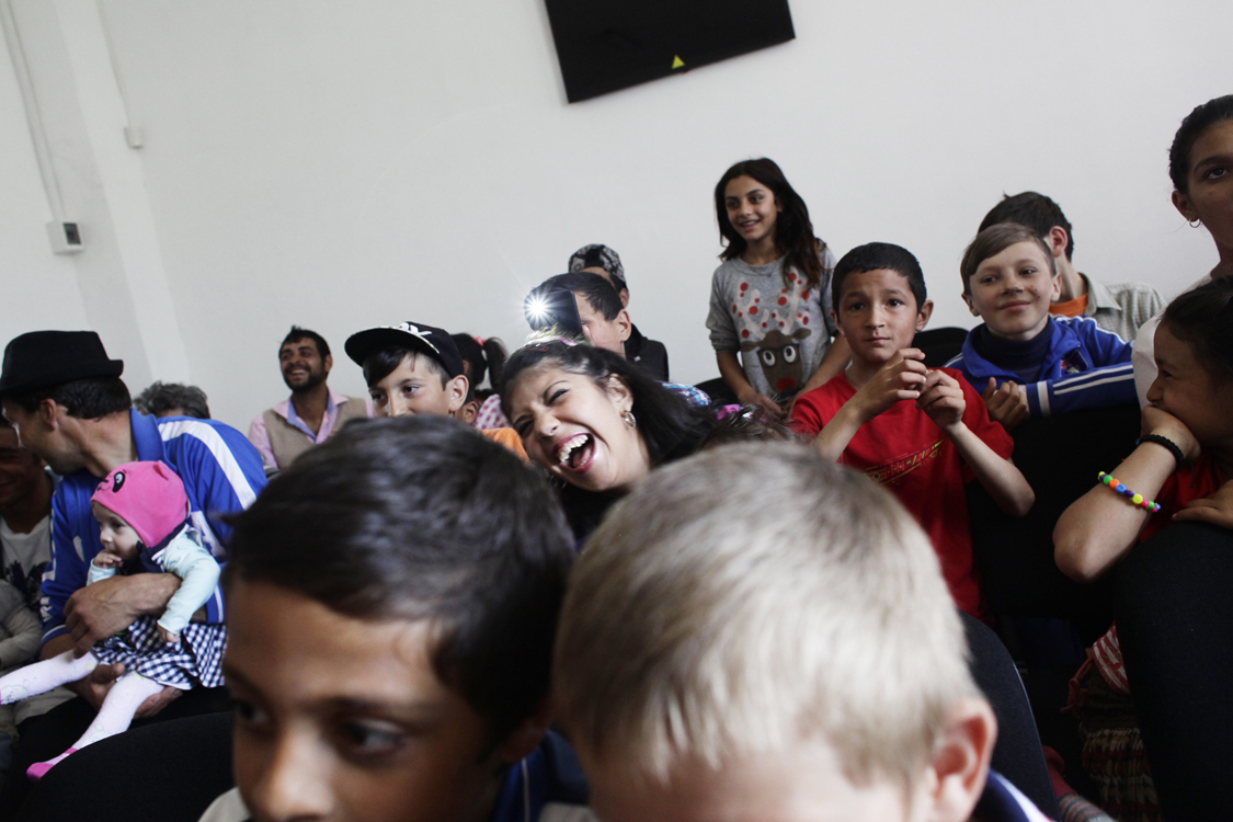 Youth in a poor Roma community laugh during a performance of theater forum play Cristina's story, directed by Mihaela Drăgan, in Cucova, on April 17th 2016. The play talks about violence against women, discrimination and the challenges of migration.