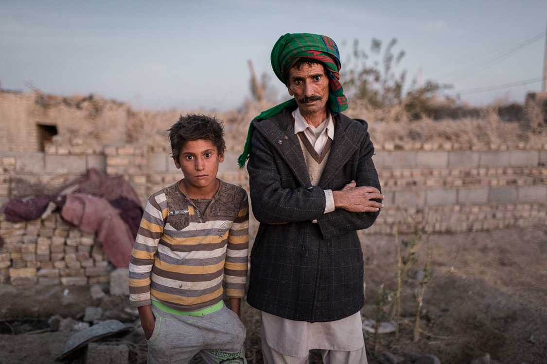 A fisherman poses for a portrait in Ali Akbar town, a small town near Zabol. He has almost quit fishing as there is no water in the lake anymore. His grandson (left) might not have the option to be fisherman, yet there are no many other options for a job in the area.