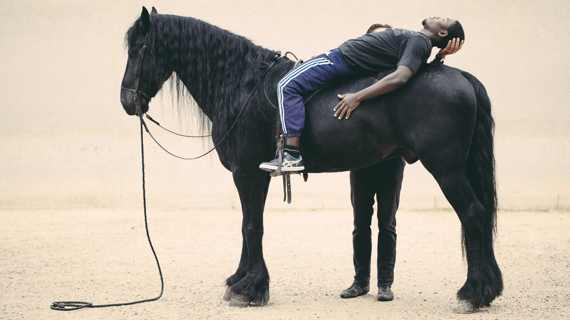 France, Marseille, 30 september 2014.The inmate is lying on the horse to learn to completely let his fears and trust the animal.Francesca Todde / NOOR