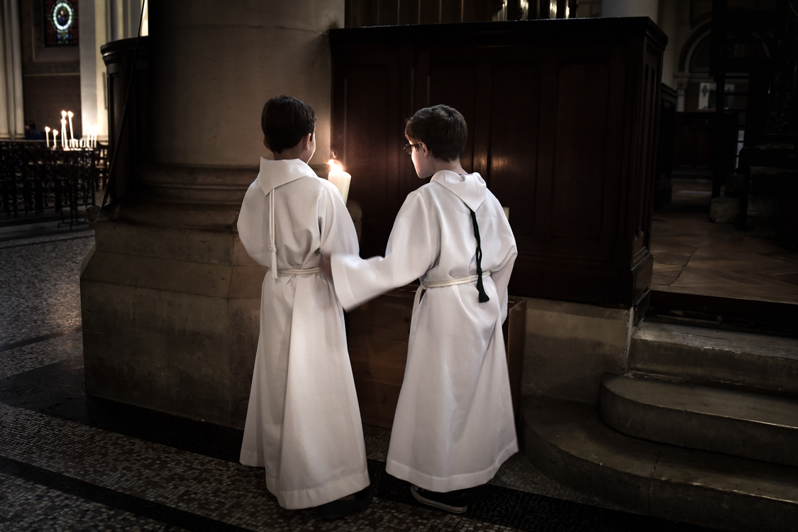 Two young children participate at the sunday mass at Saint-Ambroise's church.