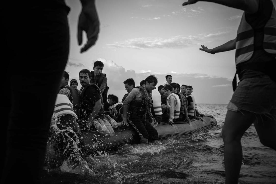 Refugees arrive via boat and land on the shores of Lesbos, Greece. Aid workers rush to assist them off the boat.