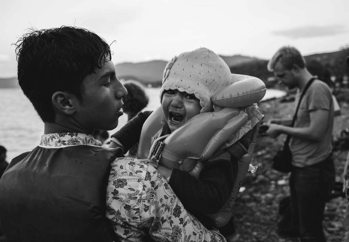 An Afghan refugee lands on Lesbos, Greece, holding his sister