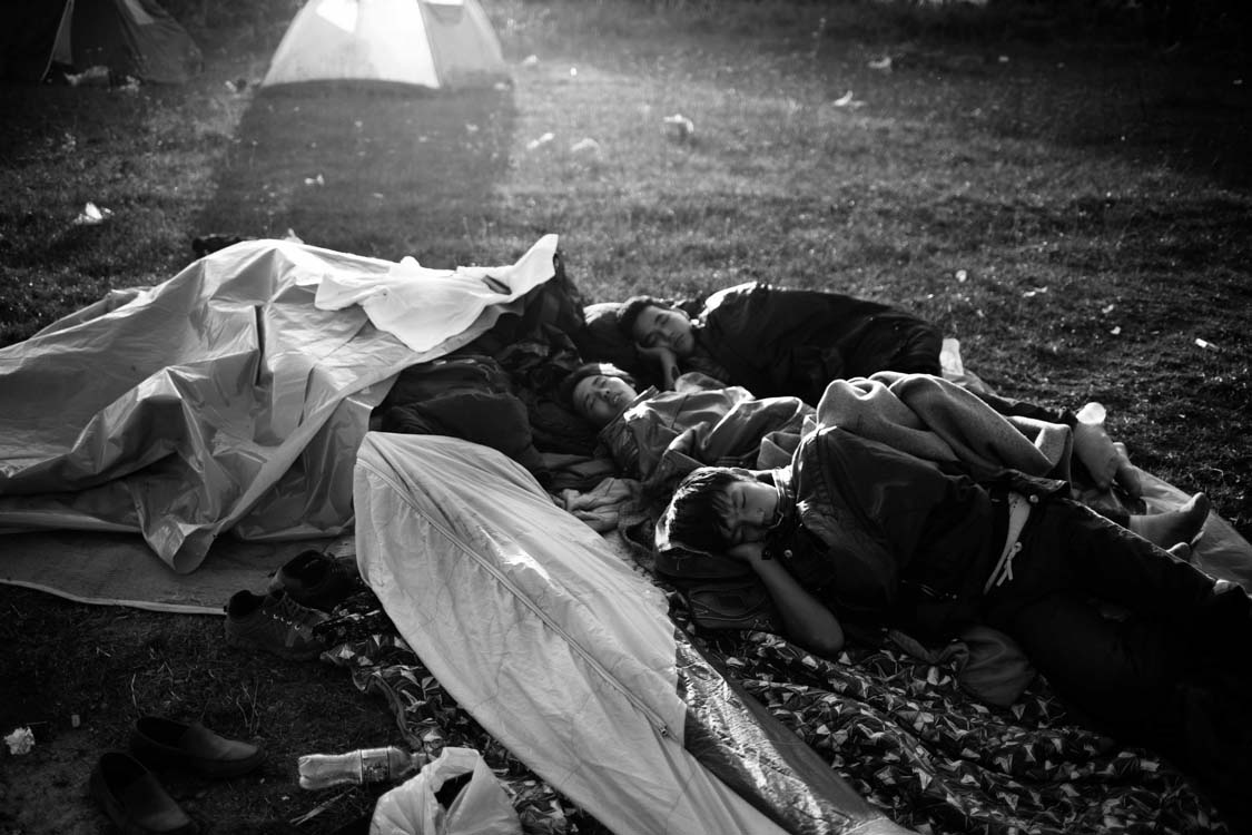 A group of Afghan refugees rest in the light of the setting sun. Preševo, Serbia. October.2015.