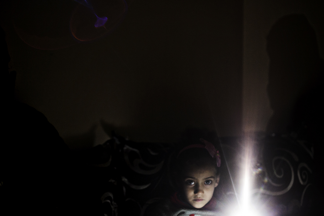 Sarah, a six-year-old Syrian refugee in Turkey. When I met Sarah in the Çankaya area of Izmir, the entire street was dark because of electricity failure. Sarah and her sister, Fatima, lit the room with mobile phones while telling their story. After their family left Syria, they lived in Lebanon before trying to reach Europe. They are one of the relatively few refugee families who, stuck in Turkey, received registration cards to settle down there because the girls went to school. One of the main difficulties for Syrians looking for work in Turkey is the language barrier. Both Sarah and Fatima speak Arabic, English and Turkish and help other family members to learn Turkish. They were invited to teach languages to other refugee kids at school and will start to give classes in spring.