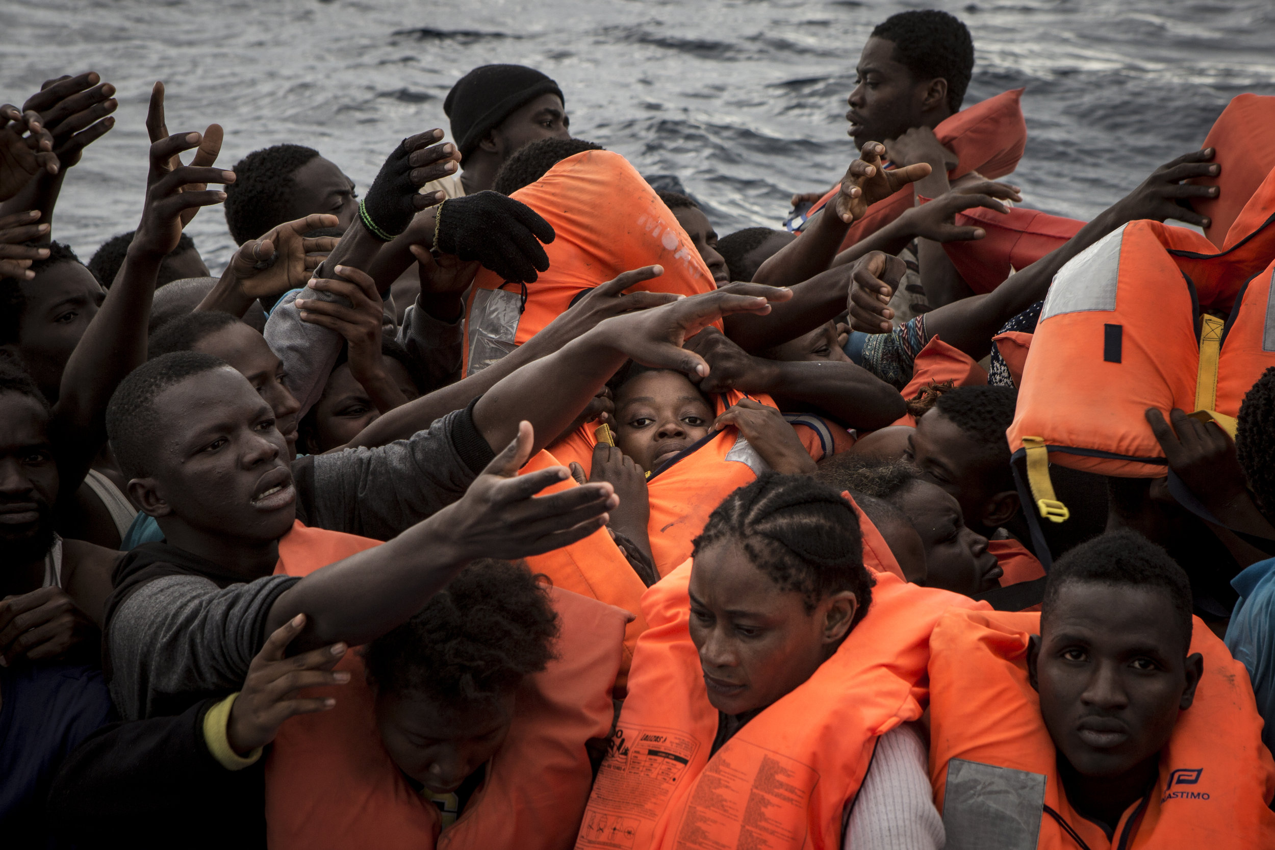 Rubber boat full of migrants as life jackets are being distributed by the MOAS crew. As they often don't have life jackets and do not know how to swim, the first priority if making sure everybody is given a floatation device.