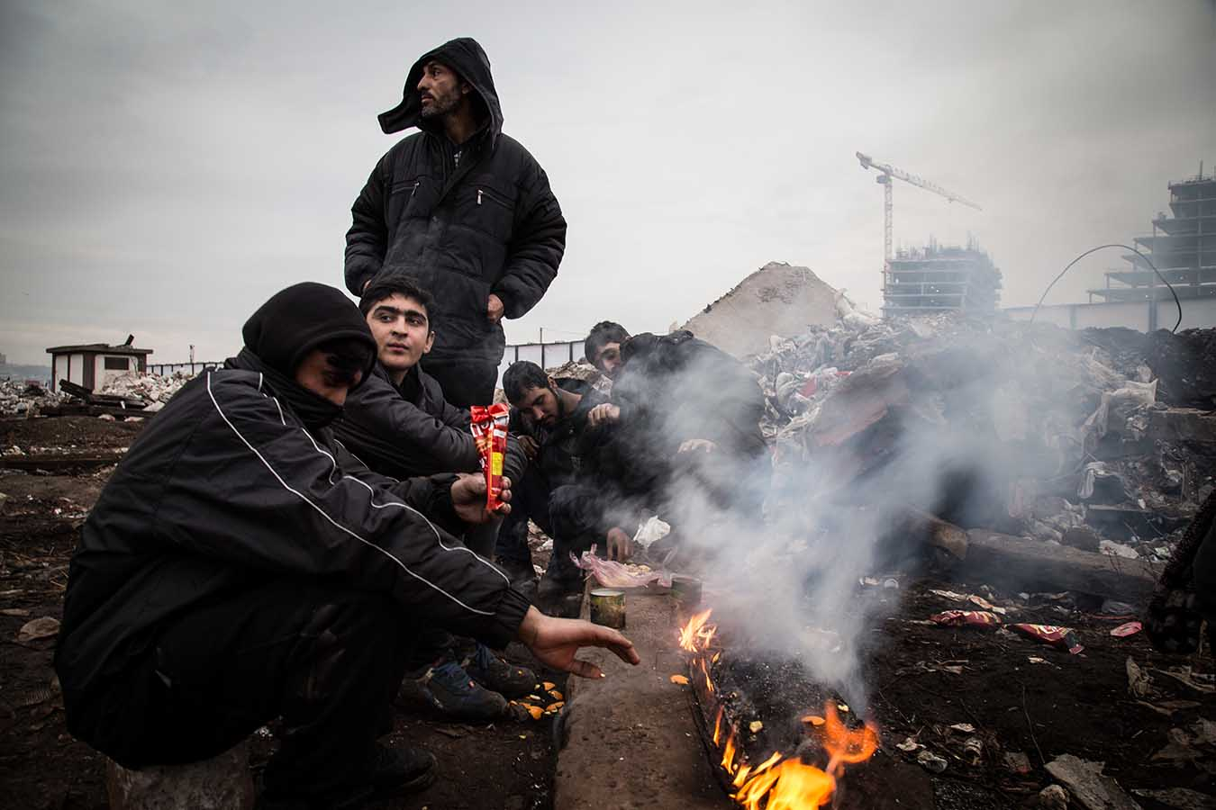 """Afghani migrants warm themselves sitting around an open fire, just outside the """"Barracks"""", a derelict complex of industrial building in the area of Belgrade's Central Station.  Since Summer 2016, an increasing number of migrants have been stuck in Serbia as a result of the shuttering of the Western Balkan Migration route. Belgrade, Serbia, February 1st 2017."""