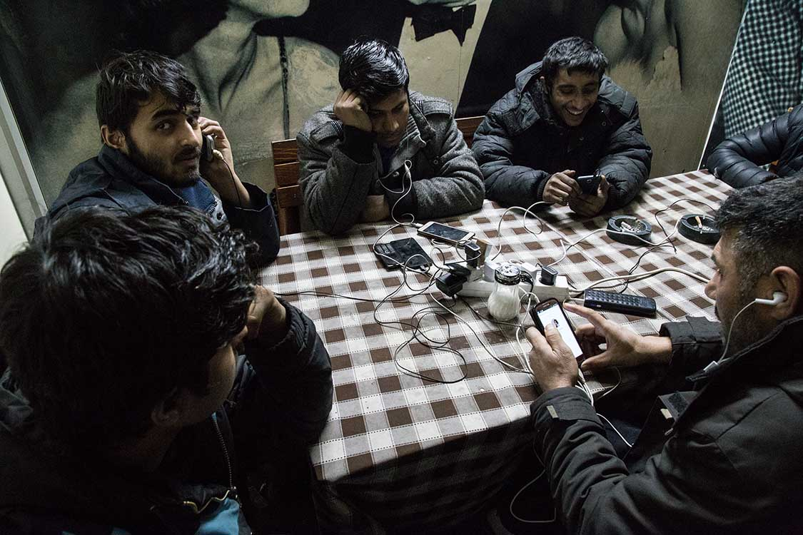 """Refugees staying in the """"Barracks"""" recharge their phones at the local station cafè, in Belgrade, Serbia. Mobile phones are often the only way for refugees to stay in touch with their families and their smugglers, the only way out of Serbia. ------Since Summer 2016, almost 8,000 people have been stranded in Serbia, as the result of the shutdown of the Western Balkan migration route taking refugees from the Middle East to Central and Northern Europe."""