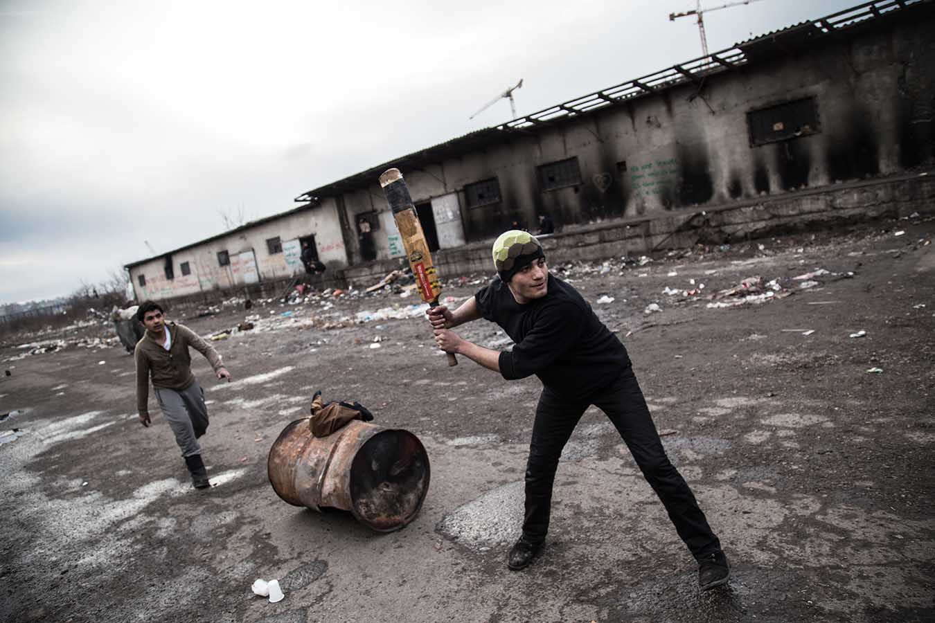 """Refugees play cricket in one of the former loading bays of the """"barracks"""", once an industrial complex, now a makeshift camp, in Beblgrade, Serbia, where almost 1,300 refugees are sleeping rough."""