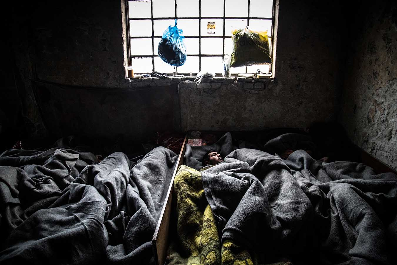 Refugees sleep rough, inside one of the abandoned warehouses in the area of Belgrade's central station, where nearly 1,300 have found refuge from the harsh Serbian winter as they way to cross into Northern and Central Europe.
