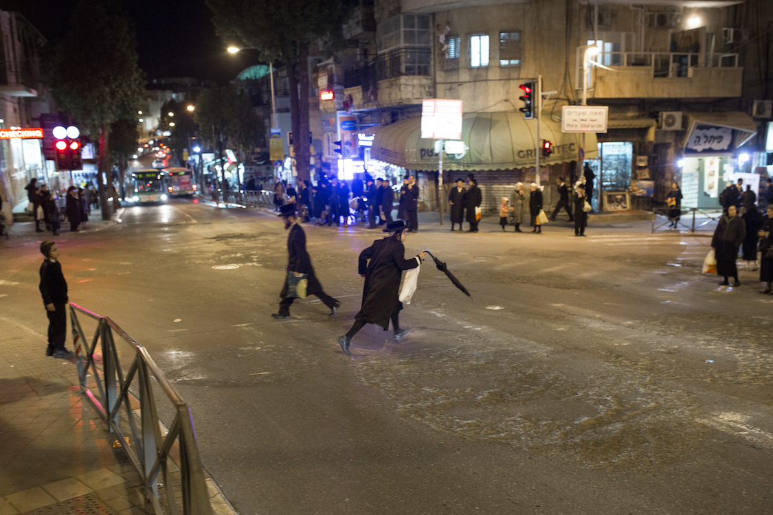A young Ultra Orthodox Haredi runs over the main cross that connects the big Ultra Orthodox neighbourhoods like Meah Shearim, in the heart of Jerusalem on 9th January, 2016. Most of the Ultra Orthodox Areas are divided between the main Family tribes and origins. When visiting the neighborhood, women and girls are urged to wear what is deemed to be modest dress (knee-length skirts or longer, no plunging necklines or midriff tops, no sleeveless blouses or bare shoulders), men and boys are urged to avoid wearing shorts and sleeveless shirts, and tourists are requested not to arrive in large, conspicuous groups. Photo by Sebi Berens