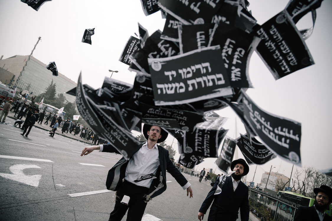 A young Ultra-Orthodox Haredi throws a bunch of flyer on a protest in Jerusalem on 2th March, 2017,  at a bill that would cut their community's military exemptions and end a tradition upheld since Israel's foundation. Ultra-Orthodox leaders had called on their men, women and children to attend the protest against new legislation ending the wholesale army exemptions granted to seminary students. Police said hundreds of thousands took part in the prayer. Israeli media estimated that between 250,000 to 400,000 attended. Photo by Sebi Berens